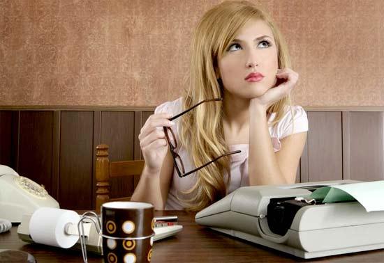 Chica blogger pensando como rentabilizar su Web frente a una maquina de escribir