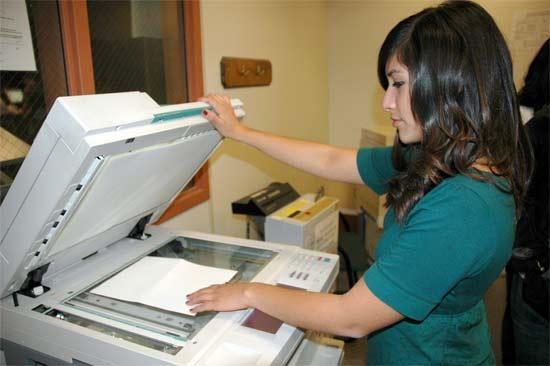 Chica copiando contenido en una copiadora tradicional